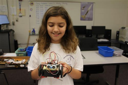 Student demonstrating Makey Makey banana piano