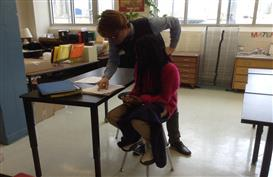 Mr Rose works with a student on her rough draft letter