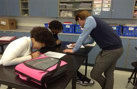 Mr Rose working with a student on his paper