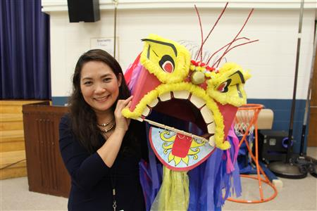 Ms. Monton holds a dragon prop from the play
