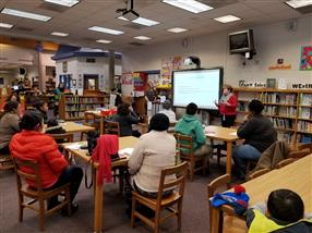 Dr Gladstone, principal, talking to parents at the Literacy Meeting in the Media Center