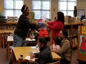 A parent at the literacy meeting receiving the door prize
